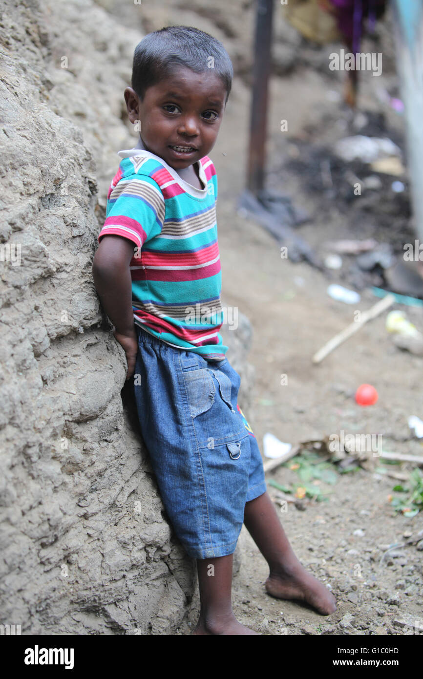 Pune, India - July 16, 2015: A poor Indian boy standing at a construction site where his parents work in India - Stock Image