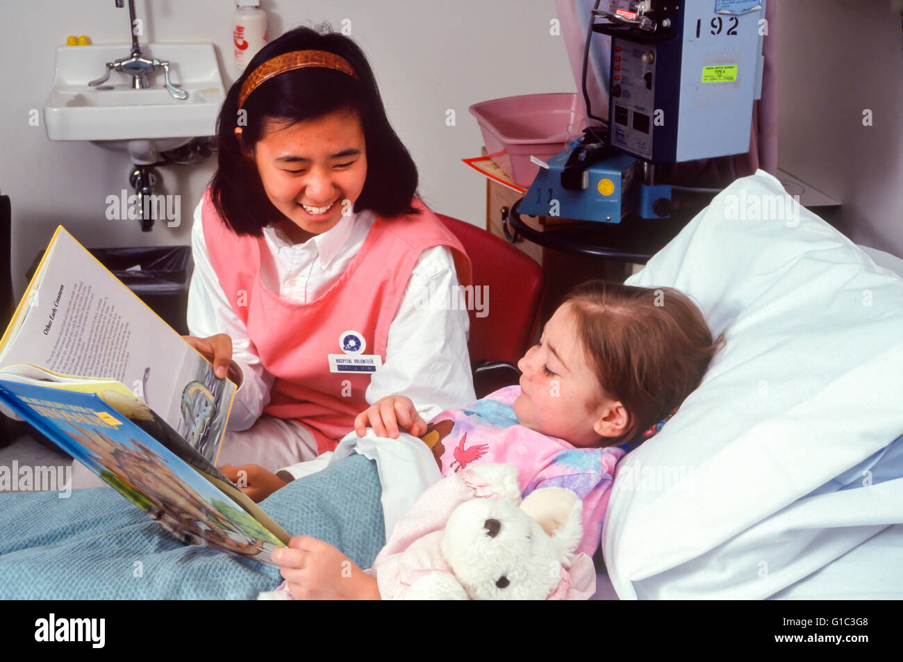 Compassionate Korean American teen cheering up and hanging out with  a very sick little girl with cancer. MR ©Myrleen - Stock Image