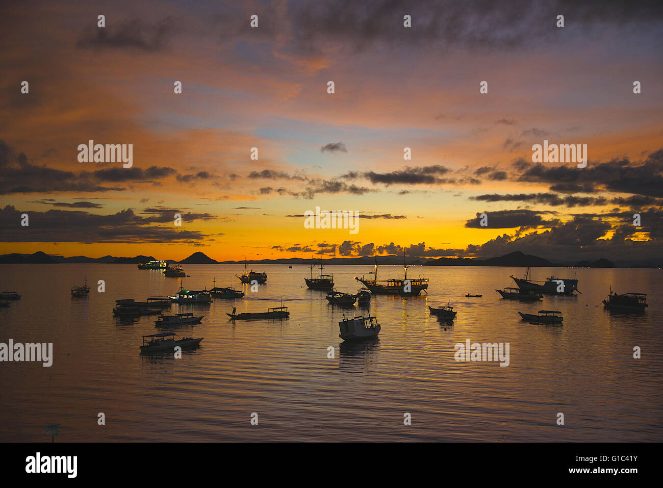 Sunset with boats Labuan Bajo port Flores Indonesia - Stock Image