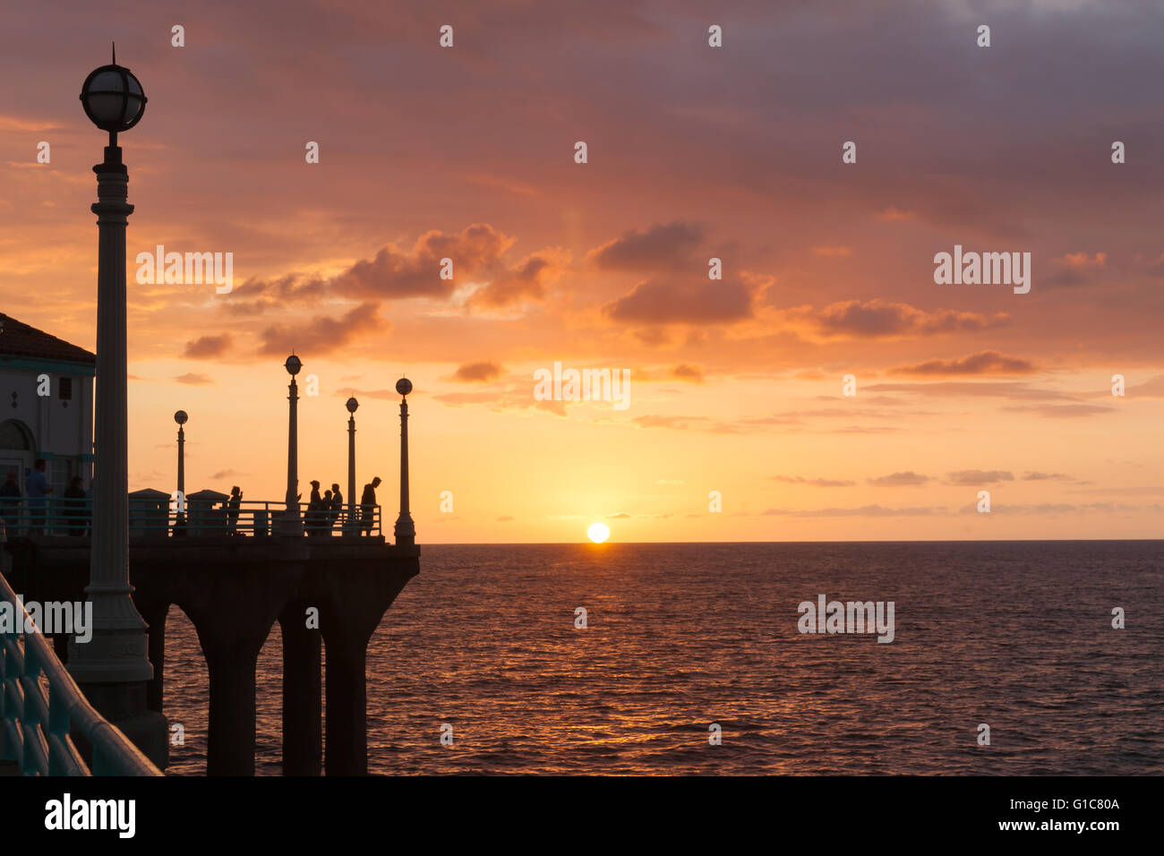 Silhouettes of people gathered to experience sunset over ocean from Manhattan Beach pier watching sunset sunset - Stock Image