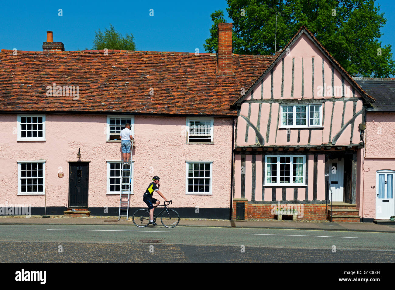 Man on ladder, repairing window frames on house in the village of Lavenham, Suffolk, England UK Stock Photo