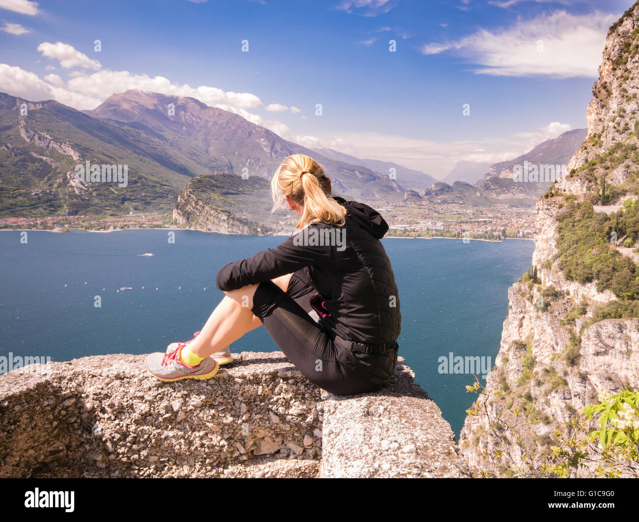 Young sporty woman admire the panorama from the Ponale trail in Riva del Garda, Italy. Stock Photo