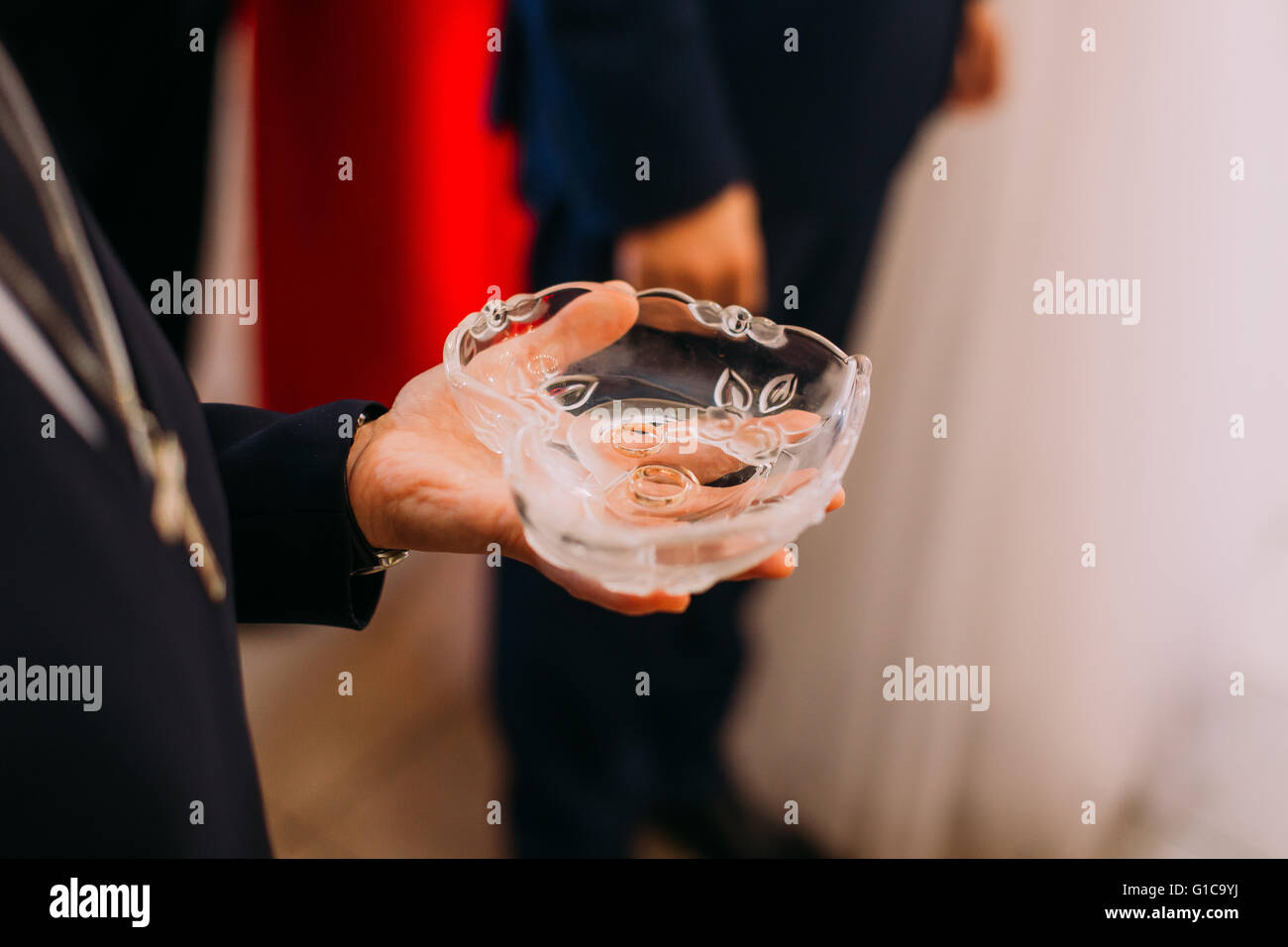 Man's hand holding heart-shaped crystal bowl with two wedding rings during the ceremony - Stock Image