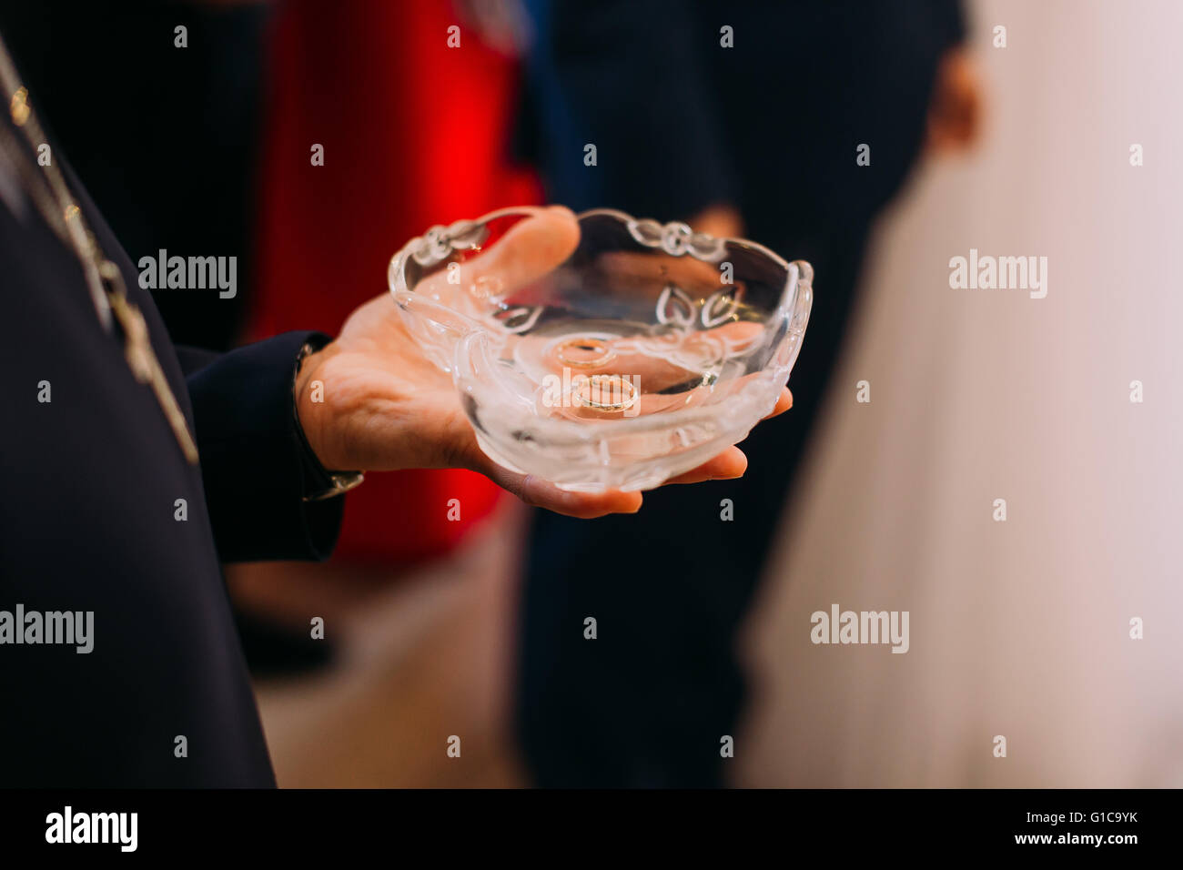 Man's hand holding heart-shaped crystal bowl with two wedding rings - Stock Image