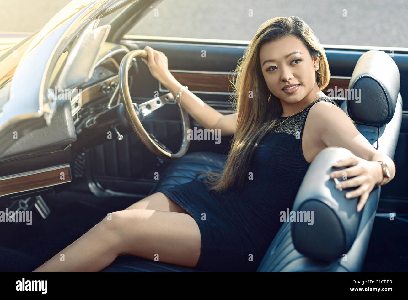 Attractive girl sitting in vintage car parked on the street - Stock Image