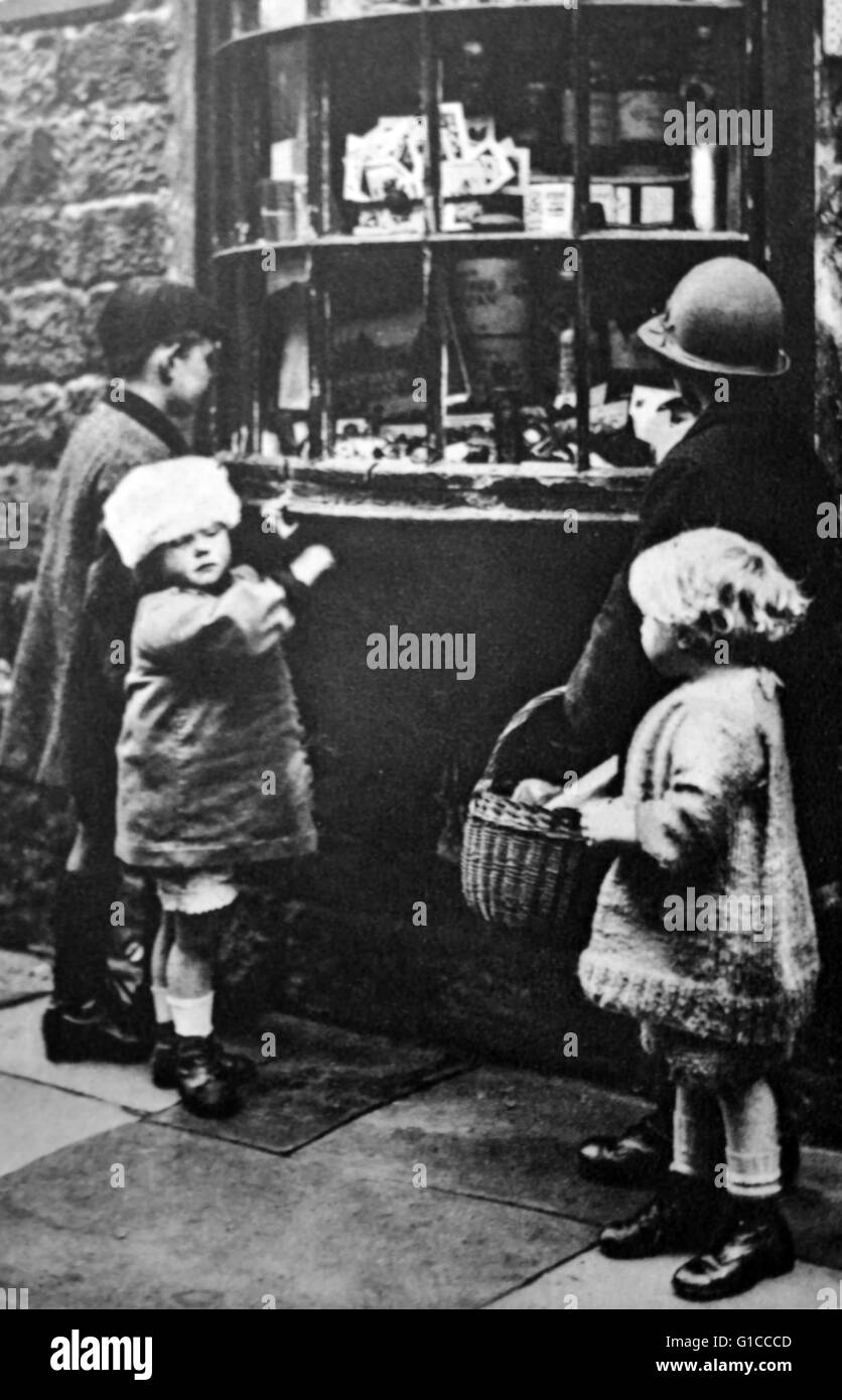 1930's children gather outside a sweet shop; England - Stock Image