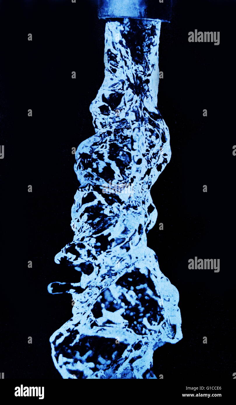 High speed 1/30,000 of a second photographic exposure showing water flowing from a tap - Stock Image