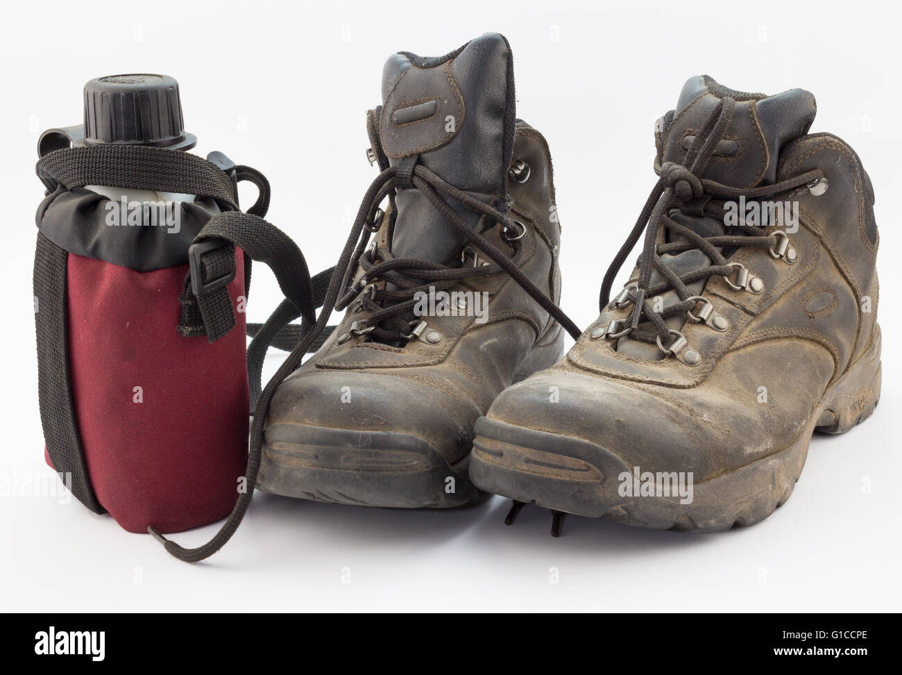 Close up of dusty hiking boots and red water bottle isolated on white - Stock Image