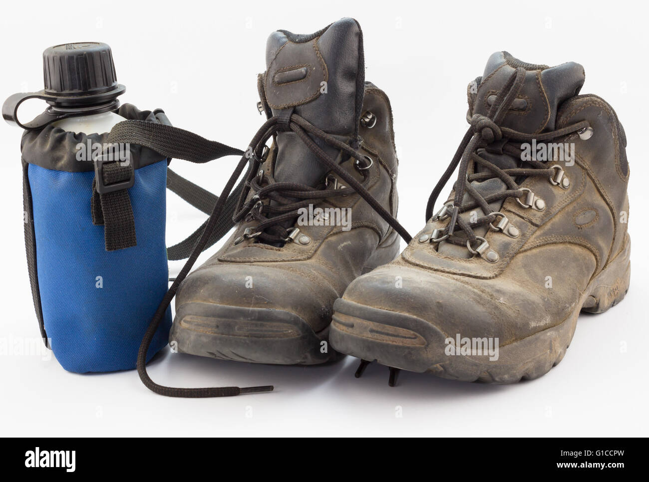 Close up of dusty worn hiking boots with water bottle on white - Stock Image
