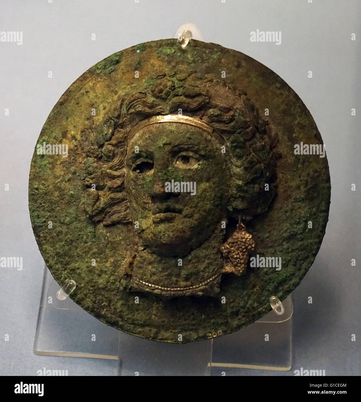 Bronze mirror cover with the head of a maenad or Ariadne. Made in Greece. Dated 330 BC Stock Photo