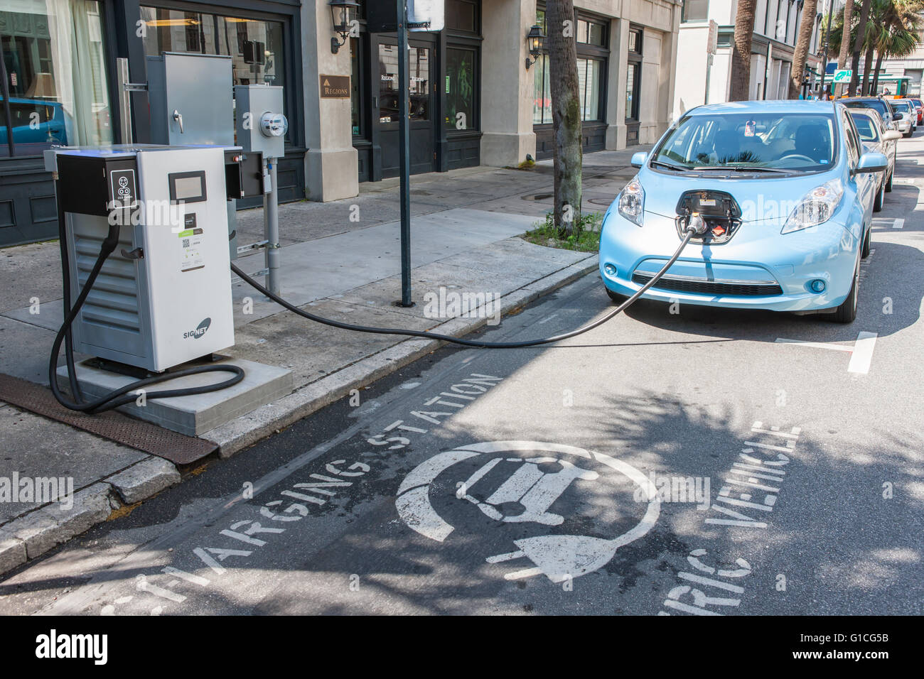 A Nissan Leaf electric car gets a charge from a public SigNet charging station on Bull Street in Savannah, Georgia. Stock Photo