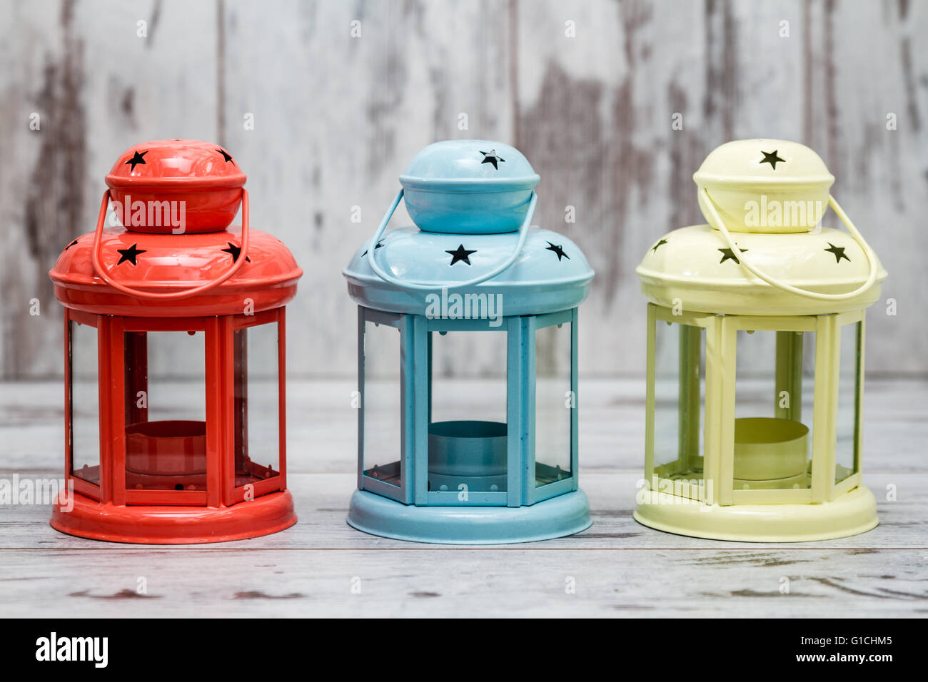 Colorful candle holders on white wooden background - Stock Image