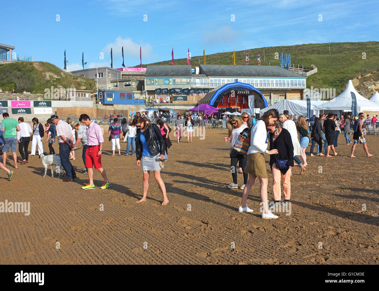 spectators at a Polo match on the beach at Watergate bay in Cornwall, UK, doing the ritual half-time divot stomping - Stock Image