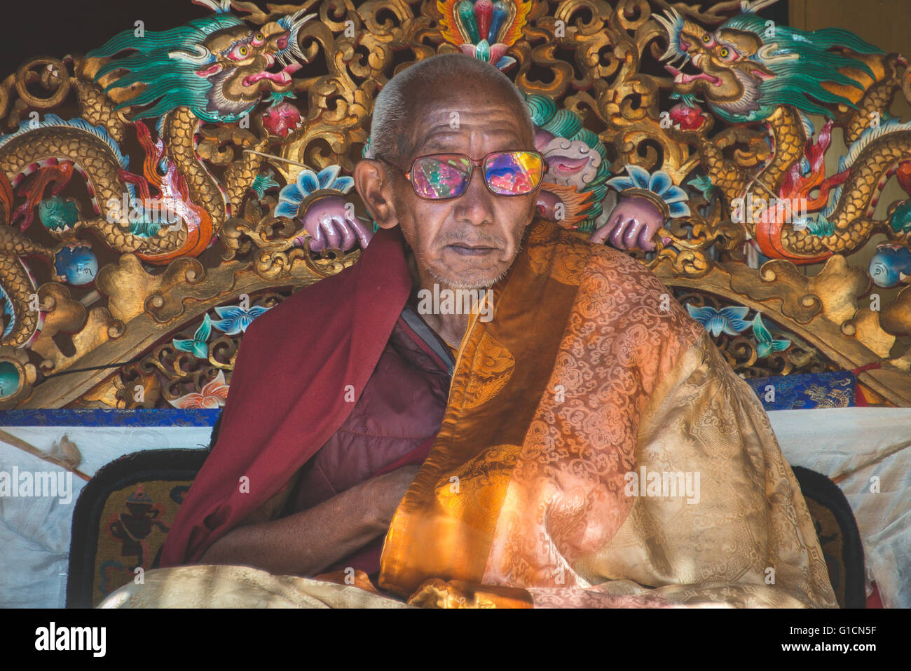 The head Lama for the Khumbu region with colourful relfections in his glasses - Stock Image