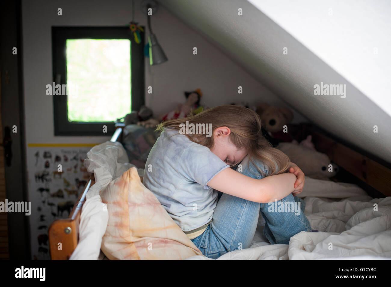 Young girl upset it her bedroom. - Stock Image