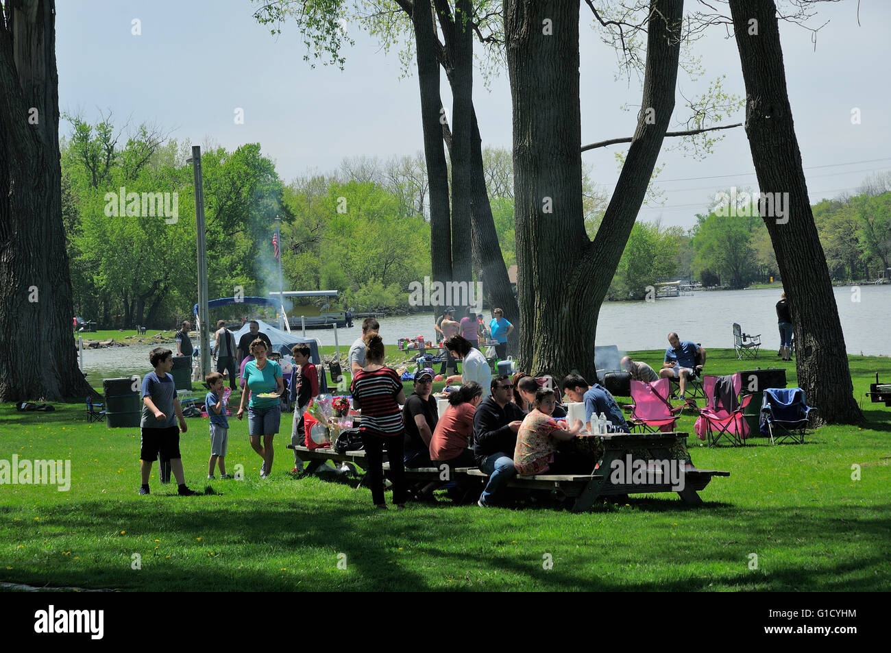 Group of people picnicking at riverside park. - Stock Image