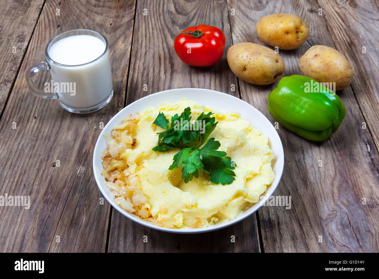 mashed boiled potato with herbs. milk and vegetables - Stock Image