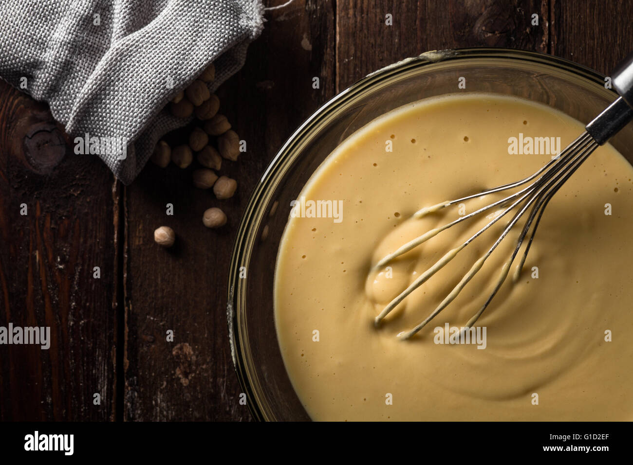 Chickpea Batter in a Bowl with a Whisk on Wood Stock Photo