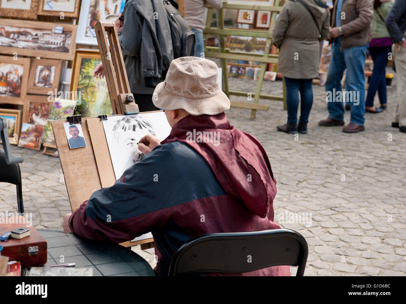 Male artist drawing man portrait from the small picture at the bazaar in Kazimierz Dolny, Poland, Europe, bohemian - Stock Image