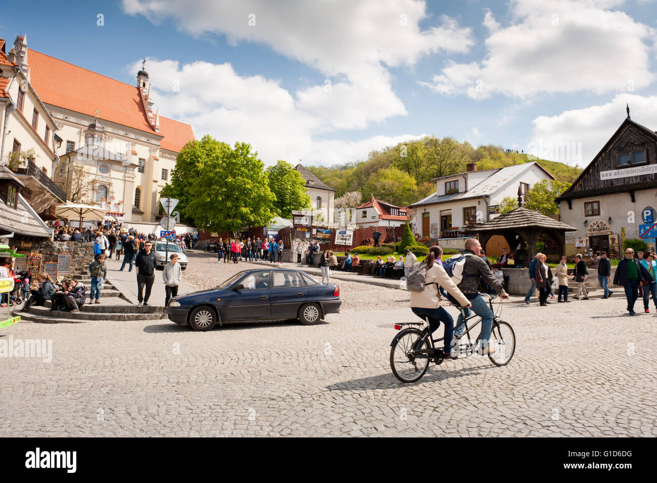 Outing at the Market square in Kazimierz Dolny, Poland, Europe, tandem bike and car vehicle people taking a short - Stock Image