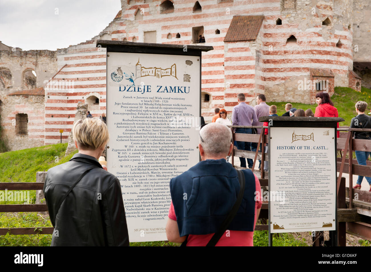 History of the Janowiec Castle, people reading the visitor information board in front of the bridge to historical Stock Photo