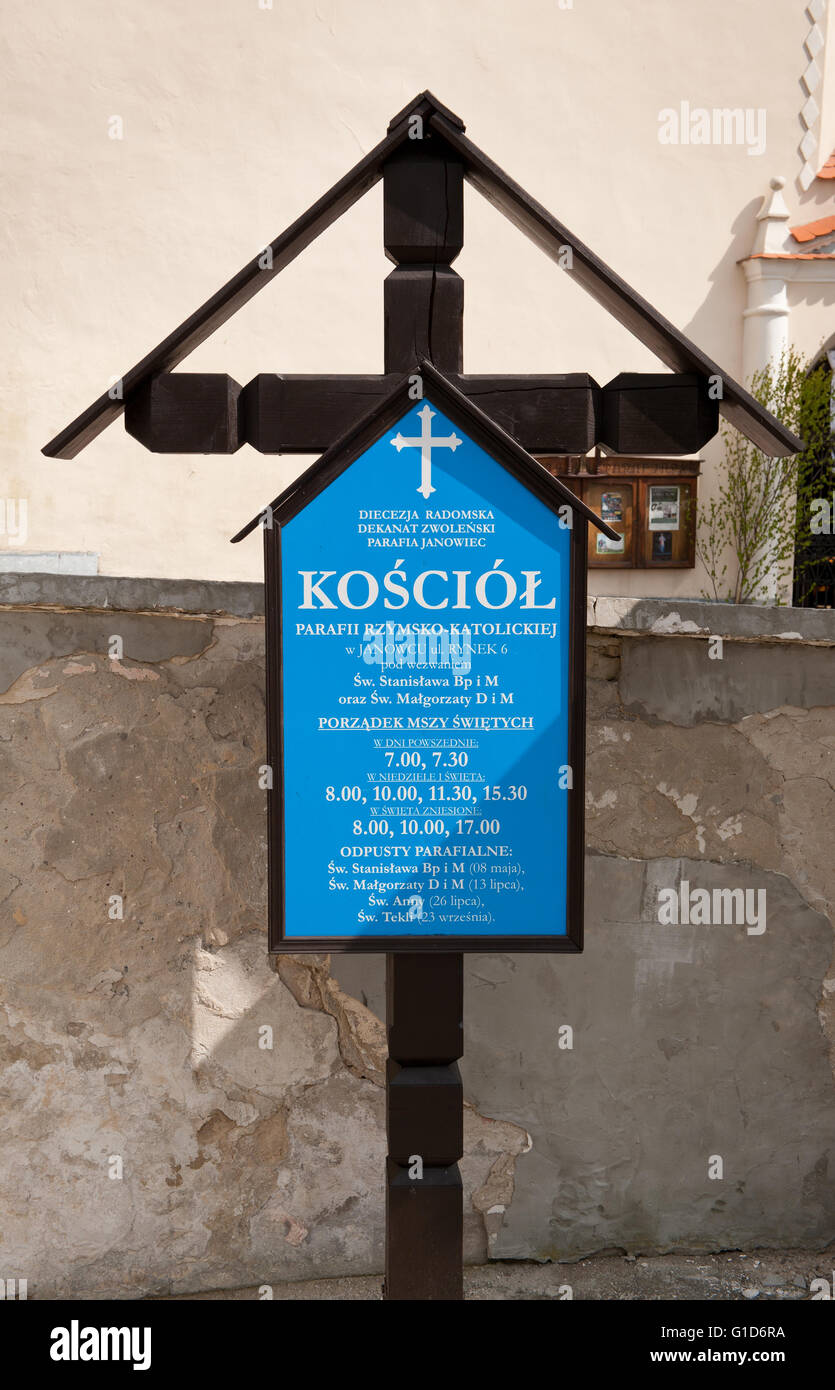 Informational cross by the church in Janowiec village, Poland, Europe, blue board with mass schedule informations. - Stock Image