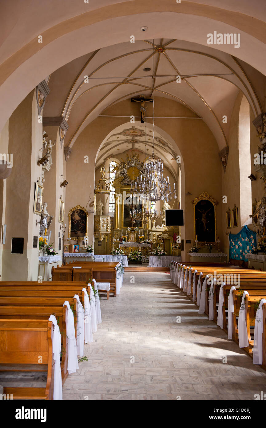 Church interior in Janowiec village, Poland, Europe, indoor view with altar and pews of Parafia sw. Stanislawa i - Stock Image