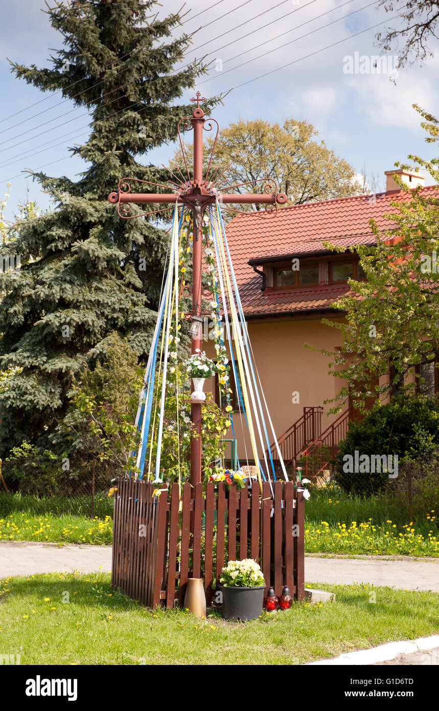 Wayside metal holy cross in Janowiec village, Poland, Europe, crucifix brown painted and decorated with flowers - Stock Image