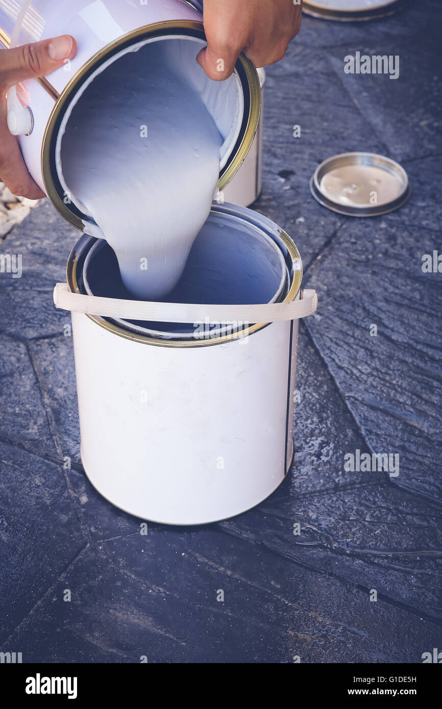 Hands of a man pouring paint, soft selective focus, toning - Stock Image