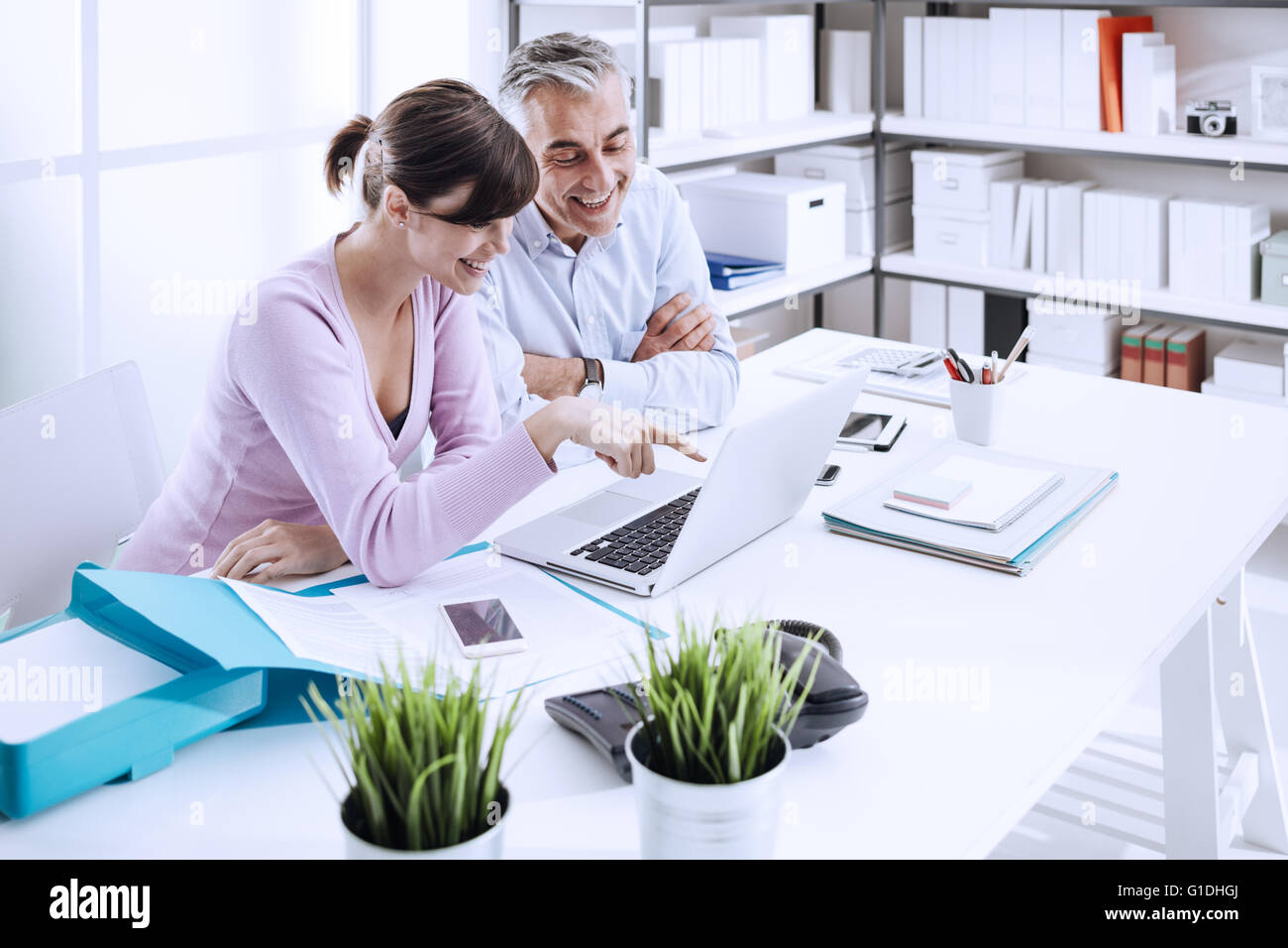 Office workers sitting at desk and surfing the web with a laptop, they are enjoying and watching funny videos online - Stock Image