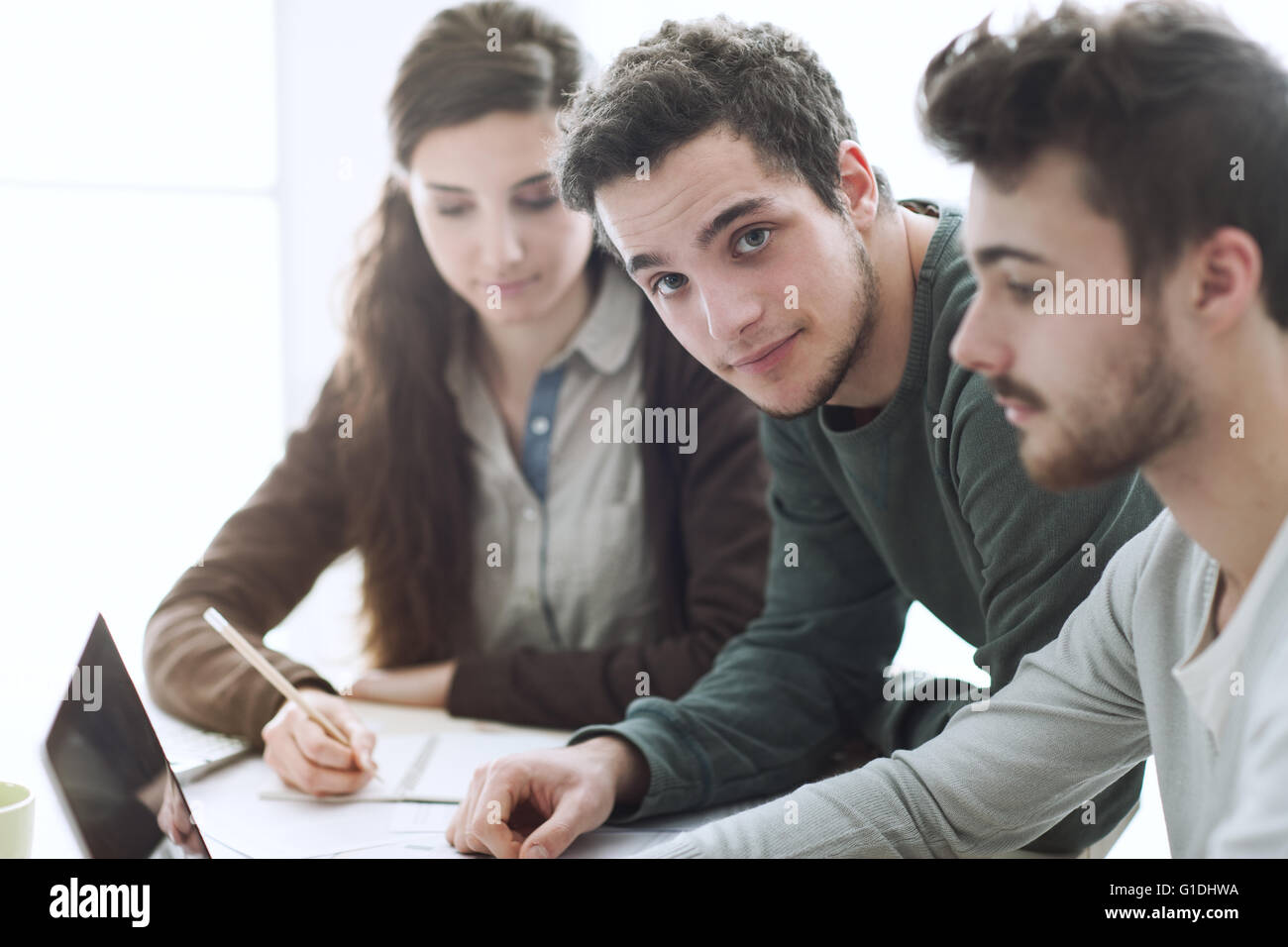Group of college students at desk using a laptop, networking and studying together, education and learning concept - Stock Image