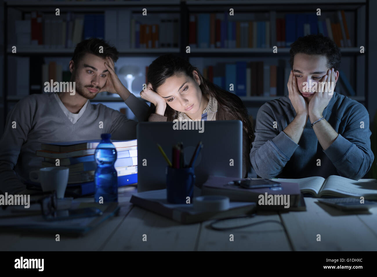 Tired students studying late at night, they are staring at the laptop screen and falling asleep - Stock Image