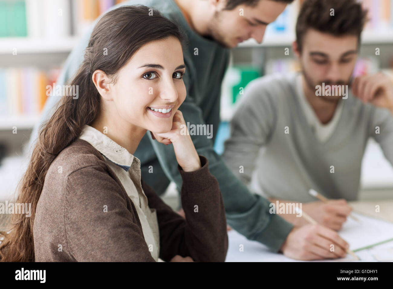 Group of smiling college students studying together at the library and working on a project - Stock Image