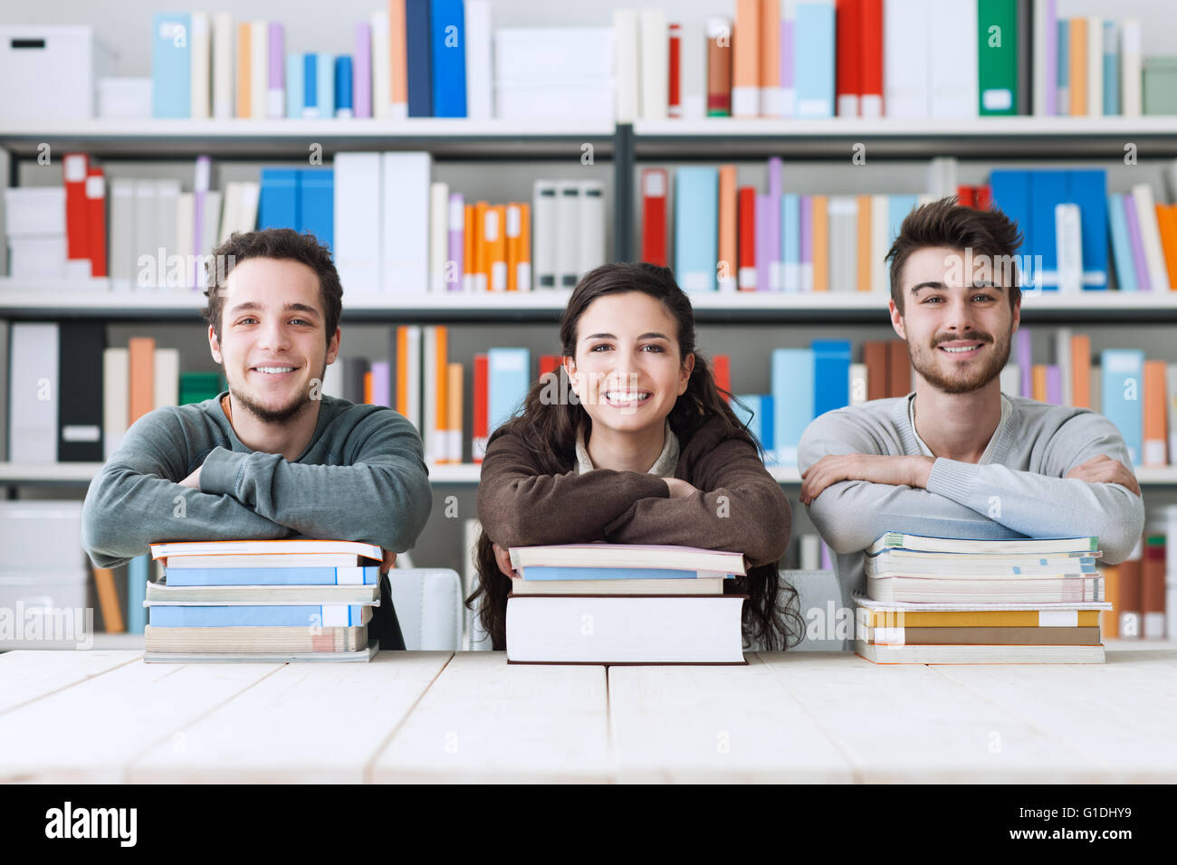 Young college students at the library studying together, they are smiling at camera and leaning on a pile of books - Stock Image