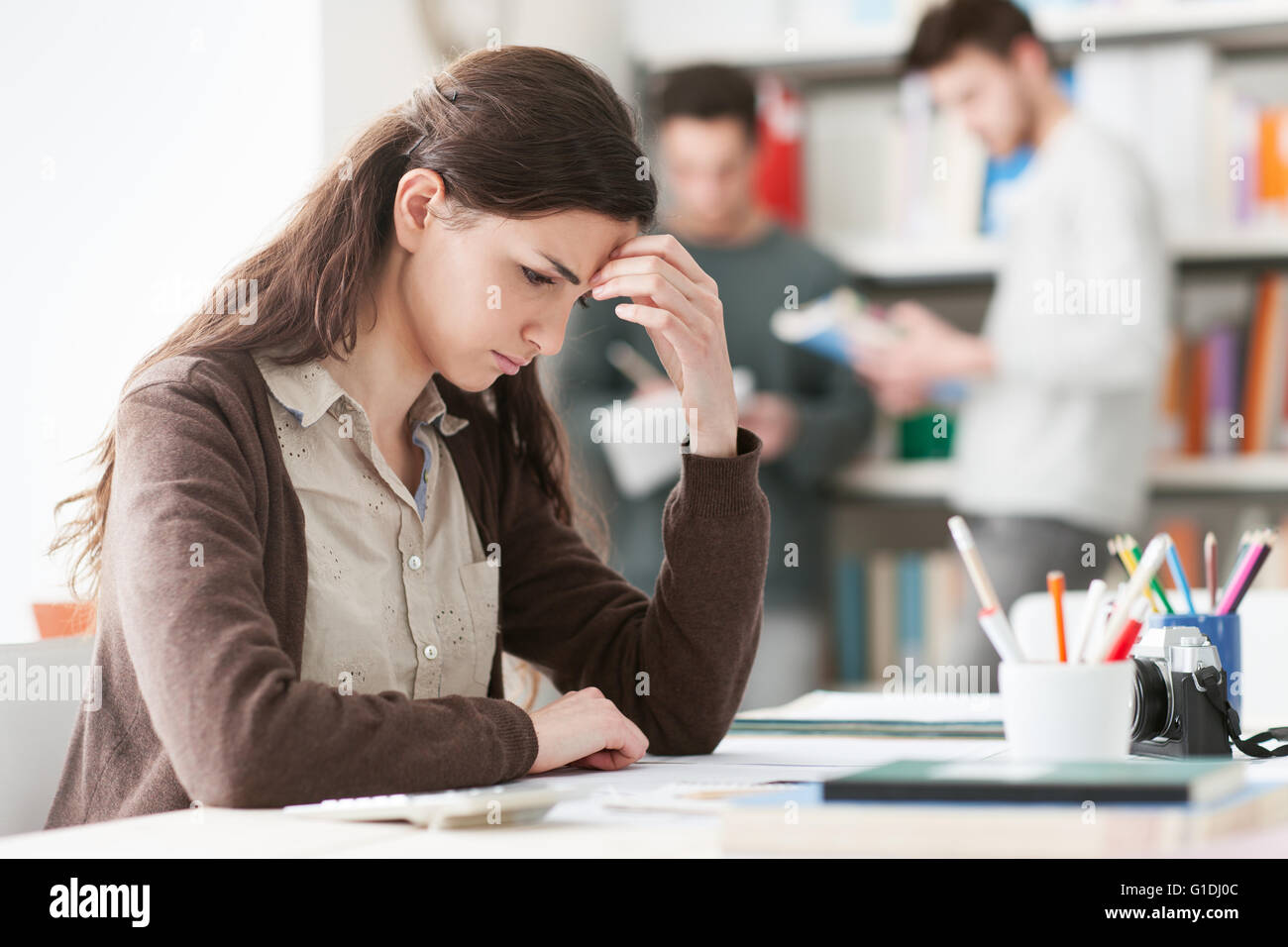 Young female student with headache, she is sitting at desk and touching her head - Stock Image