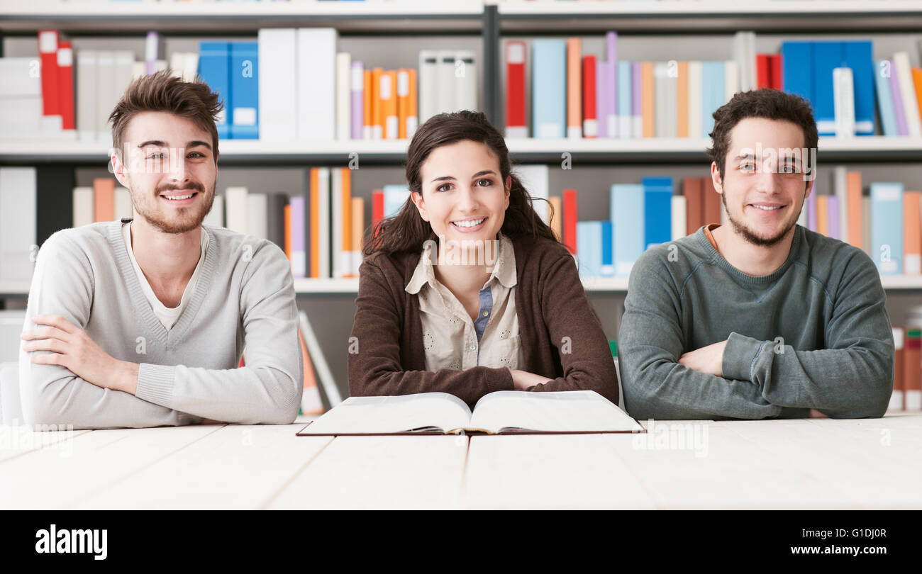 Young college students at the library studying together, they are reading a book, knowledge is power concept Stock Photo