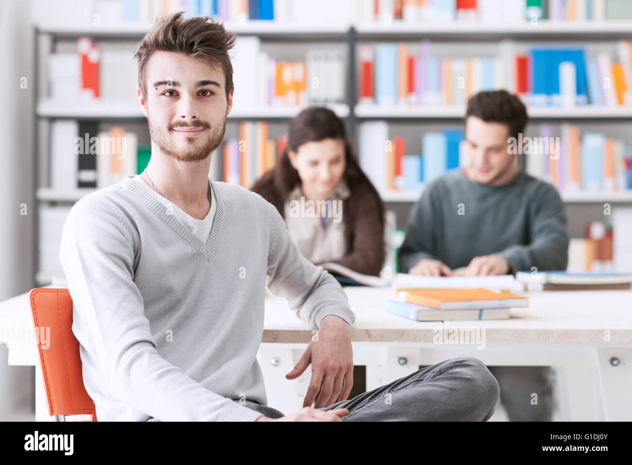 Young male students at the library smiling at camera, his schoolmates are sitting at desk on background - Stock Image