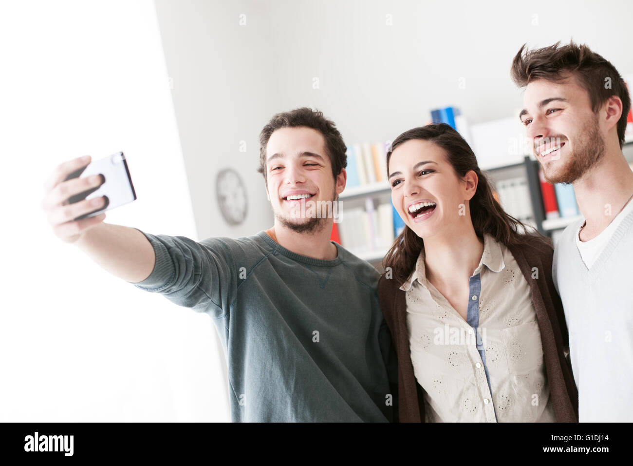 Smiling happy teenagers taking selfies with a mobile phone, sharing, technology and friendship concept - Stock Image