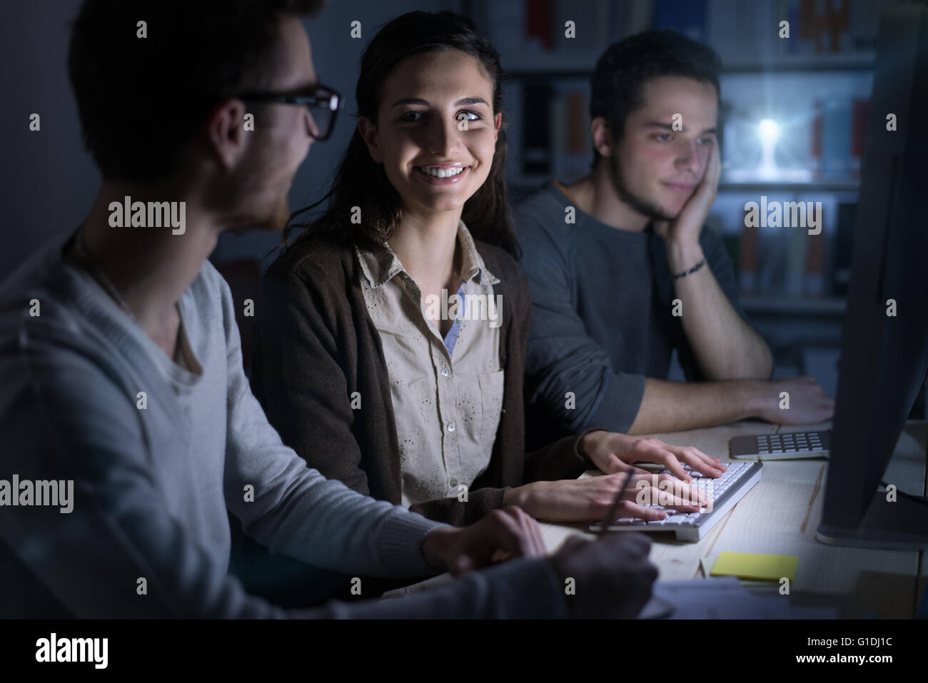 Teenagers studying late at night using a computer in a dark room, technology and communications concept - Stock Image