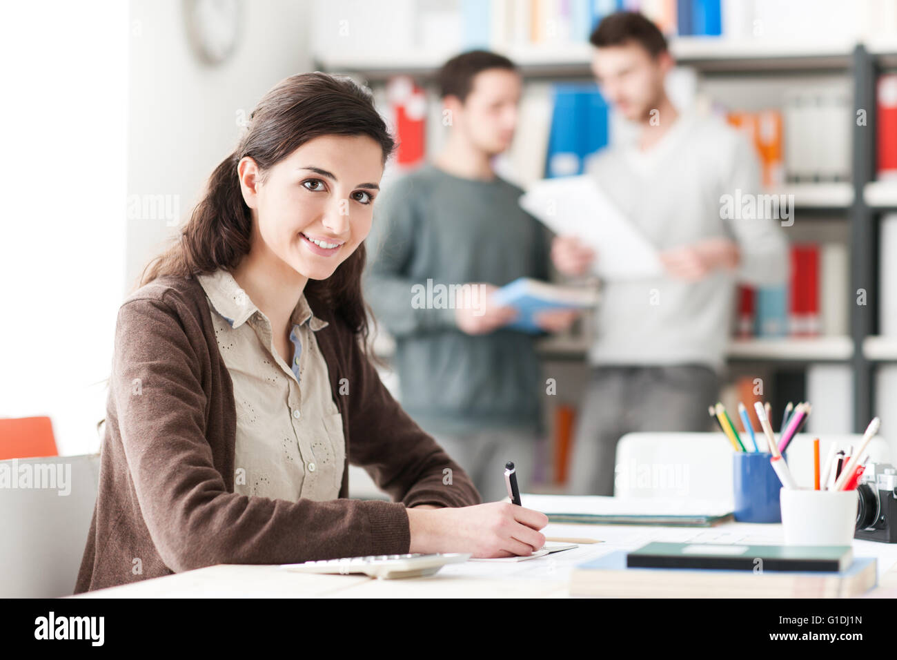 Young female student doing homework and studying at the library, students and bookshelves on background, education - Stock Image