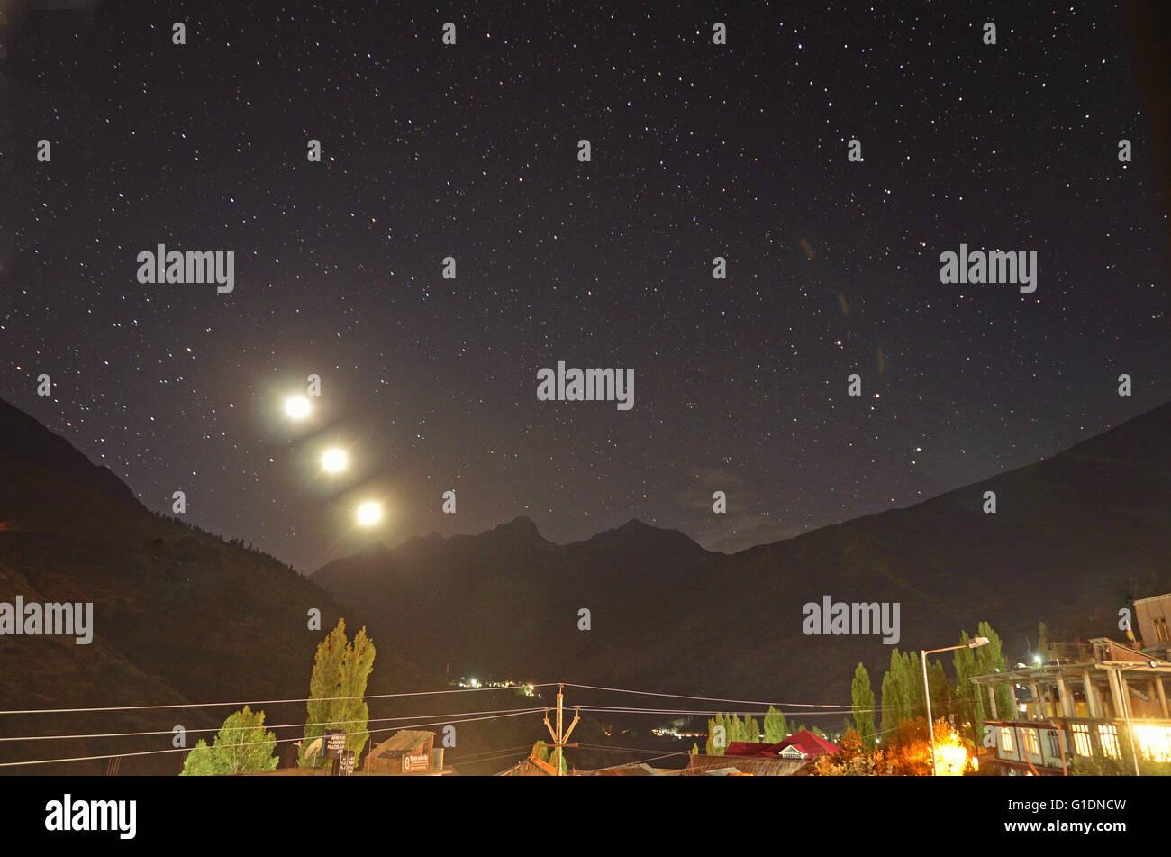 Moon sets over the Himalayan ranges, view from Keylong, Lahaul, Himachal Pradesh, India - Stock Image
