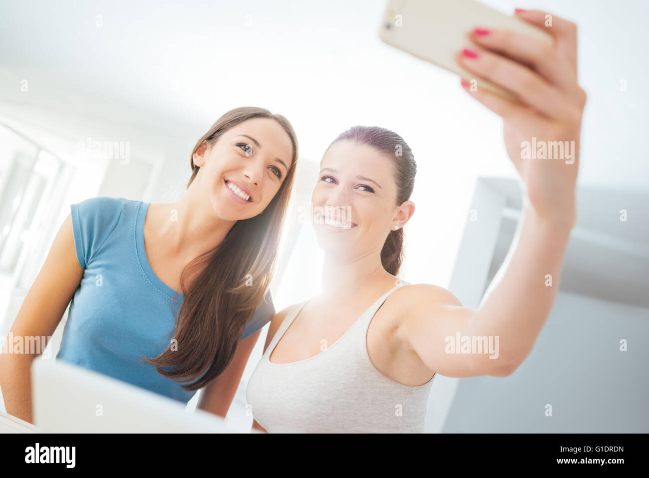 Cheerful young girls taking selfies with a touch screen smart phone and having fun - Stock Image