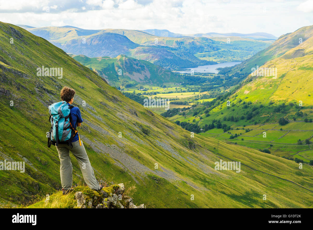 Walker overlooks Hartsop valley from above Raven Crag Threshthwaite in the Lake District, with Ullswater in the - Stock Image
