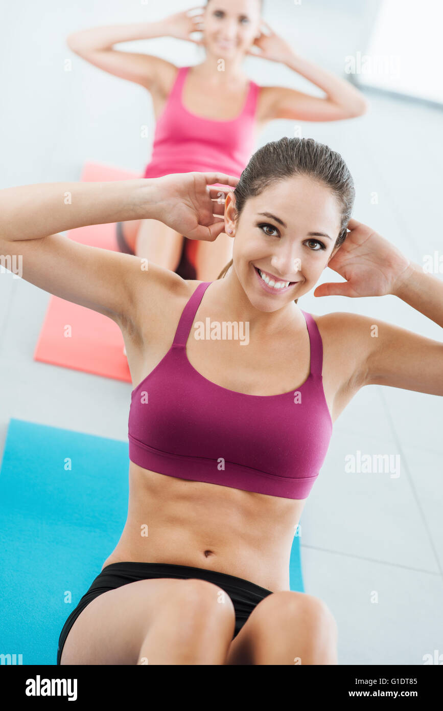 Sporty young girl at the gym doing abdominals workout on a mat, she is smiling at camera, fitness and health concept - Stock Image