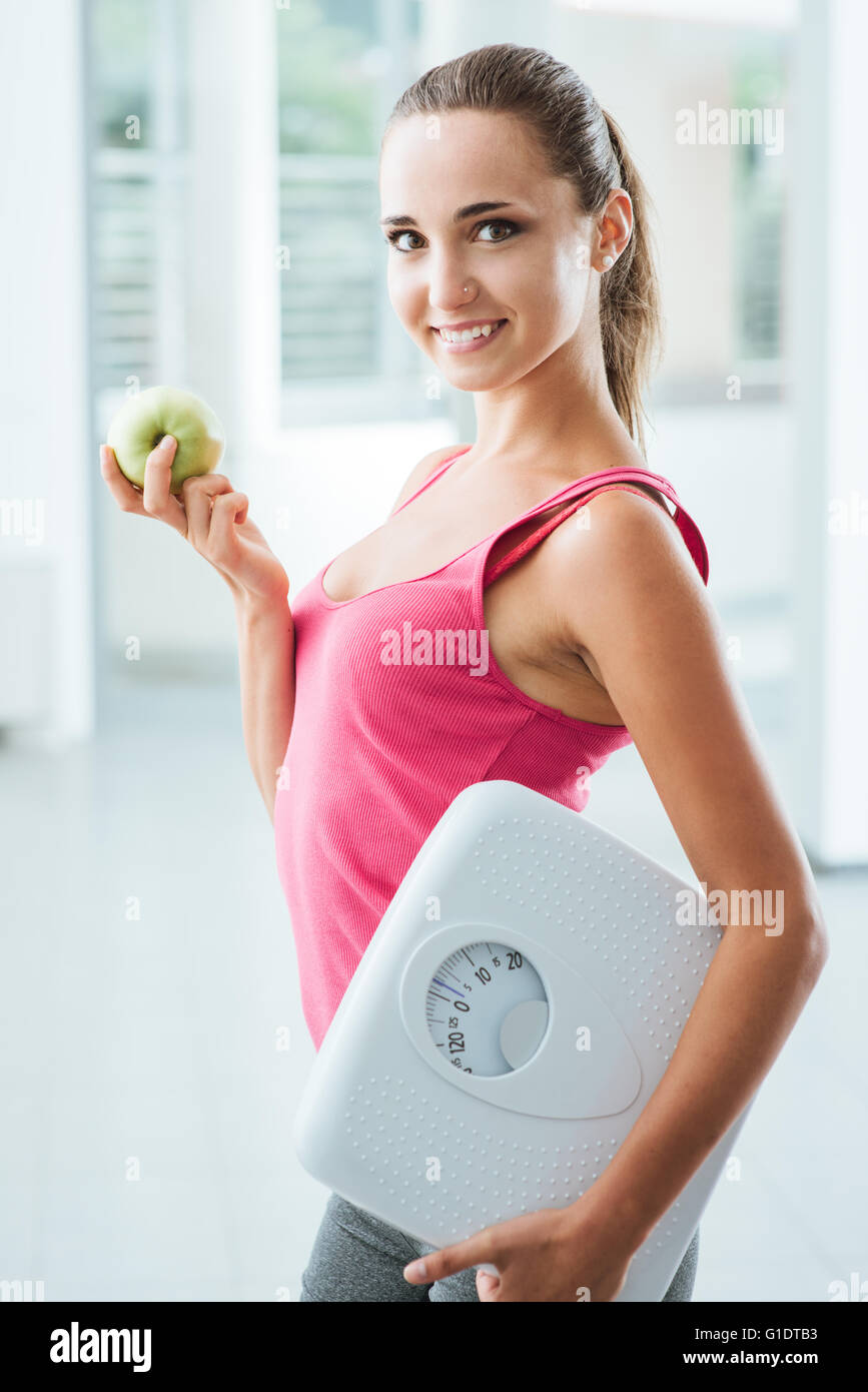 Smiling teenage girl holding a scale and a fresh apple, healthy eating, fitness and weight loss concept - Stock Image