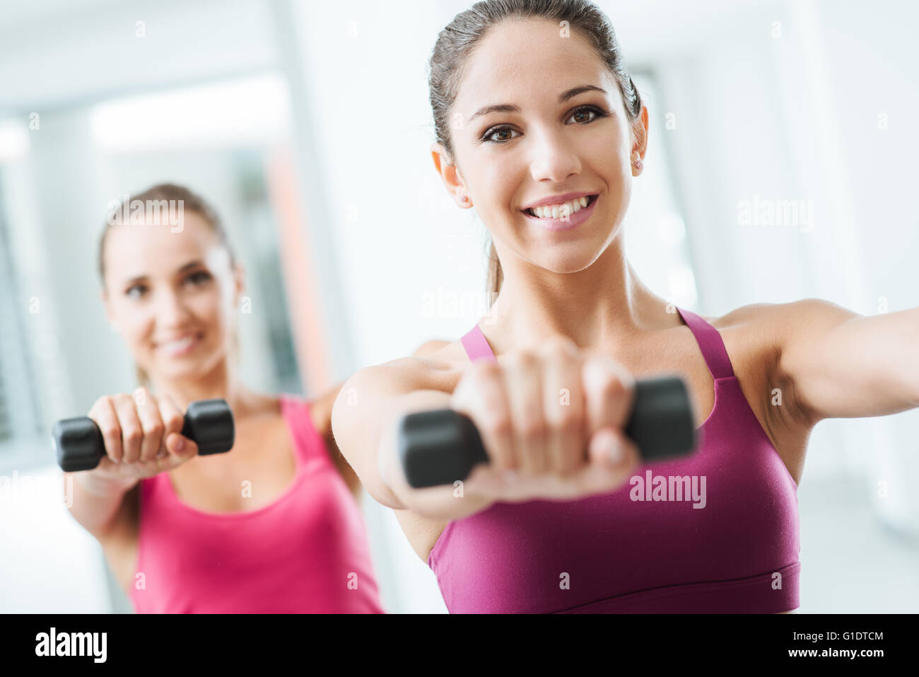 Teen sporty girls at gym exercising and weightlifting using dumbbells, body care and training concept - Stock Image