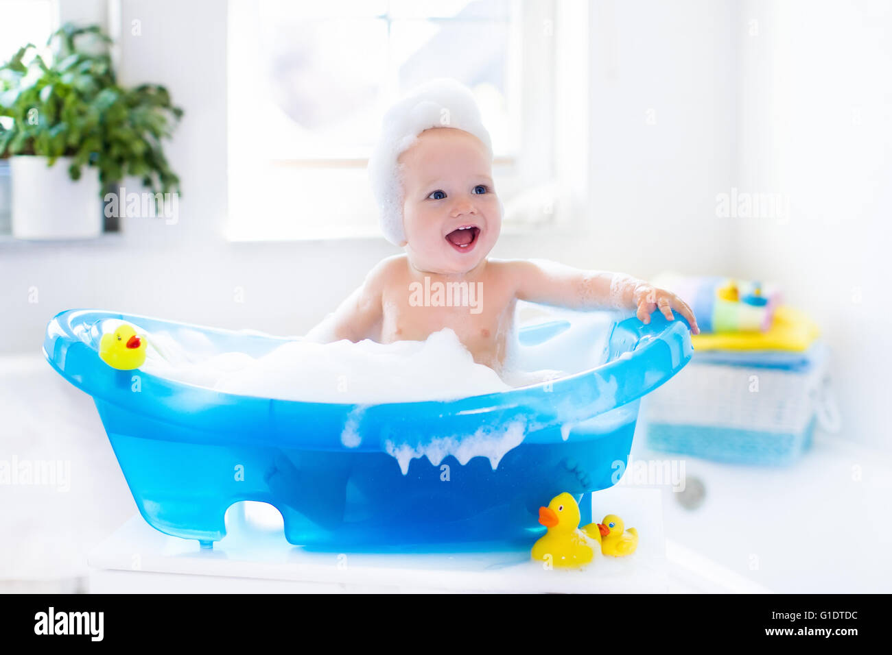 Happy laughing baby taking a bath playing with foam bubbles. Little ...