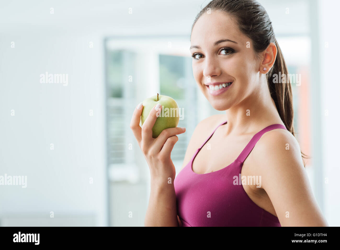Young slim woman holding an apple and smiling at camera, healthy eating and weight loss concept - Stock Image