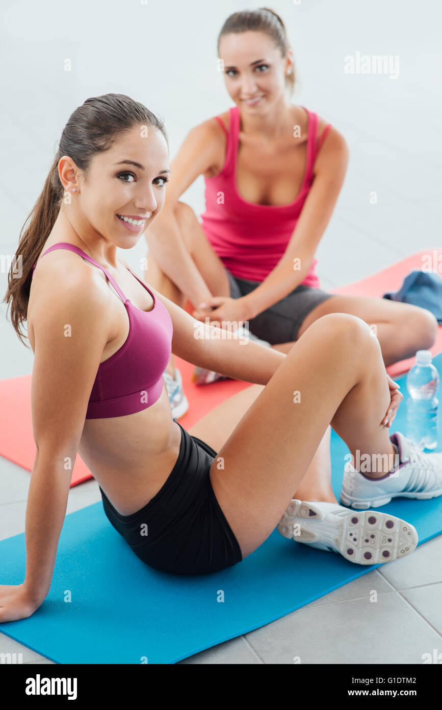 Young smiling girls at the gym sitting on mats and having a break after workout, they are looking at camera - Stock Image