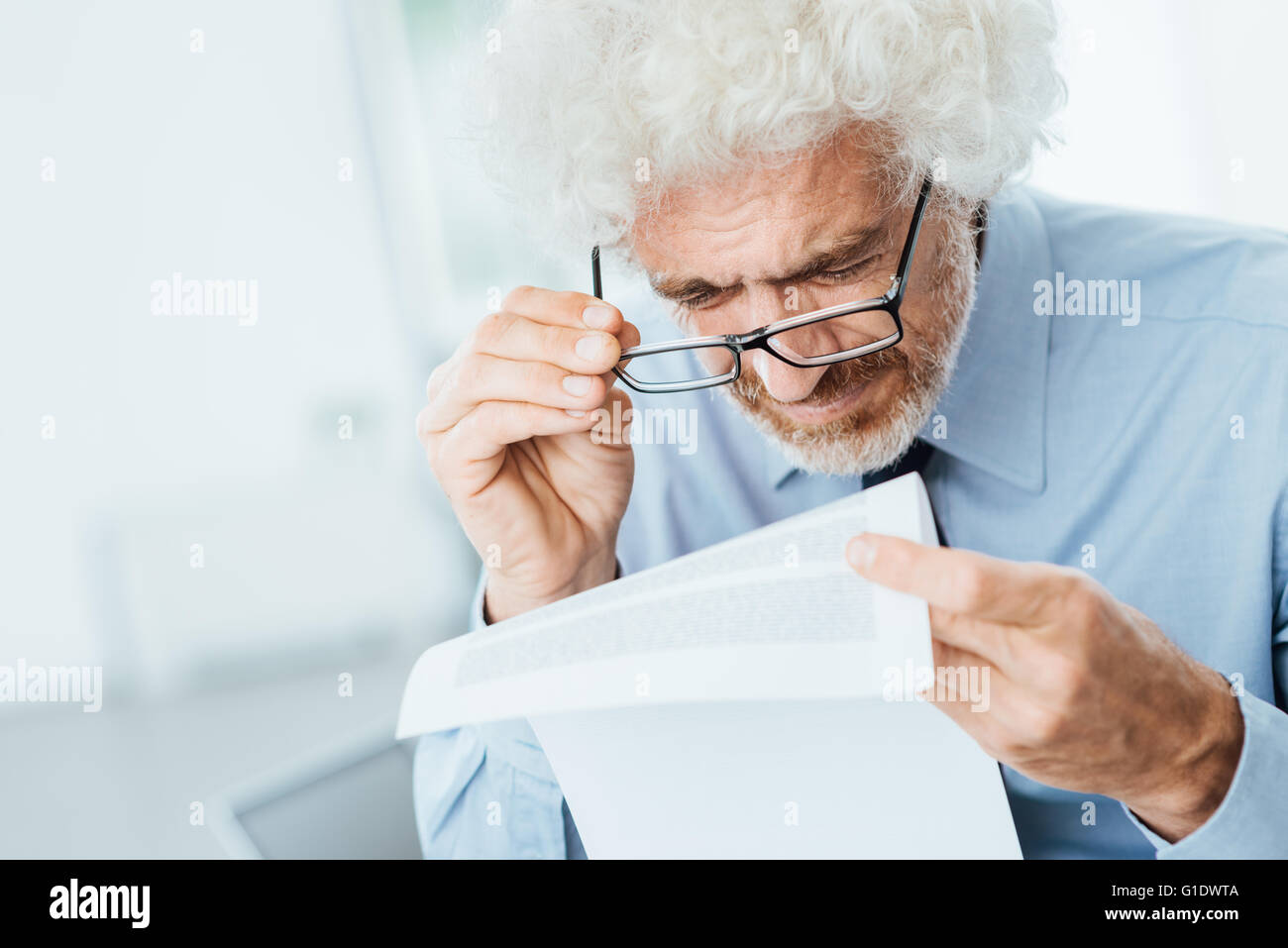 Mature male office worker having eyesight problems while reading paperwork with small text - Stock Image